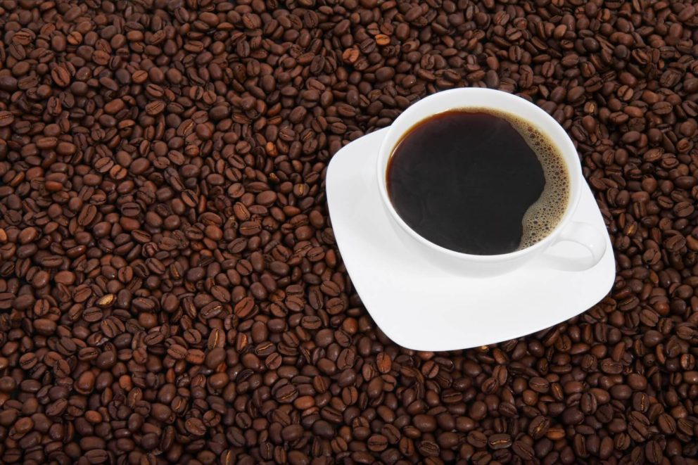 Sea of coffee beans with a cup of black coffee.